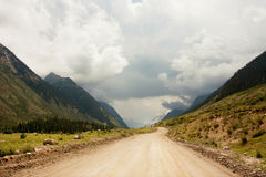Grandiose clouds over a country road in the rugged mountains royalty free stock images