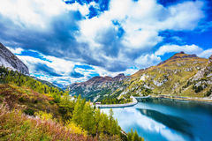 Grandiose glacial Lago di Fedaia. Grandiose glacial lake Lago di Fedaia in the Dolomites. Cloudy cold autumn day. The concept of ecological and extreme tourism Stock Image