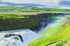 Grandiose Gullfoss in Iceland. In July raging water is shined with the bright morning sun. River banks grew with a green northern moss Stock Photography