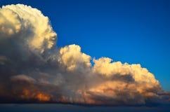Grandiose huge powerfully cumulus clouds at sunset in blue sky. Grandiose huge powerfully cumulus clouds at sunset in blue sky Royalty Free Stock Image
