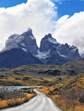 Grandiose landscape in the Chilean Andes, Patagonia. Grandiose landscape in the Chilean Andes. The road between turned yellow hills goes to snow-covered black Stock Images