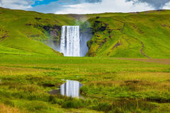 Grandiose reflection. The huge deep falls Skogafoss are reflected in small stream Stock Image