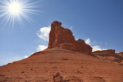 A grandiose rock from red sandstone. Monument Valley in the United States.  A grandiose rock from red sandstone and the bright midday sun Royalty Free Stock Image