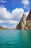 Grandiose rocks and Kelsu mountain lake against. The background of colourful dark blue sky with clouds... Kelsu, Kyrgyzstan Royalty Free Stock Photos