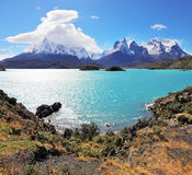 The grandiose rocks Los Kuernos are covered with ice. Magic beauty of the lake of Pehoe. The strong wind drives turquoise waves on the lake, grandiose rocks Los Stock Photo