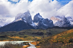 Grandiose snow-covered black rocks of Los Kuernos. Grandiose landscape in the Chilean Andes. The road between turned yellow hills goes to snow-covered black Royalty Free Stock Photography