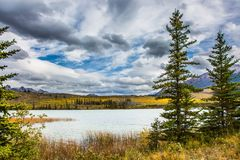 Grandiose trip to the Rocky Mountains. Cloudy Indian summer in the Rockies of Canada. Rocks and lakes under flying clouds. Concept of active and ecological Stock Photos