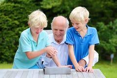 Grandkids que enseñan al abuelo a utilizar la PC de la tableta Imágenes de archivo libres de regalías