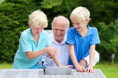 Grandkids teaching grandpa to use tablet pc royalty free stock images