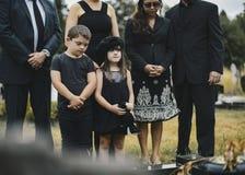 Grandkids tristi che fanno una pausa la tomba fotografie stock