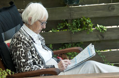 Grandm solving puzzle Stock Image