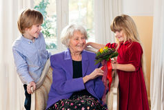 Grandma που λαμβάνει τα λουλούδια από τα εγγόνια Στοκ Εικόνα