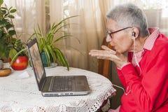 Grandma χρησιμοποιώντας το lap-top, τη κάμερα και τα ακουστικά για τις απόμακρες συνδέσεις Στοκ εικόνα με δικαίωμα ελεύθερης χρήσης