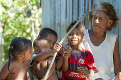 Grandma Amazonia. Grandma teaches grandchildren to shoot with bow and arrow stock images