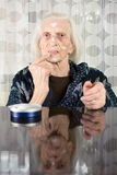 Grandma applying face cream. At home Royalty Free Stock Photography