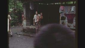 Grandma With Baby. INDONESIA, BALI, FEBRUARY 1977. Inner Courtyard Of The Tirta Empul Temple With A Bare Chested Grandmother Holding A Baby In Her Arms stock video footage