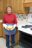 Grandma Baking Apple Pie, Kitchen, Home Cooking. Grandma shows off her apple pie baked fresh from her oven. Tasty home cooking Stock Photos