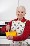 Grandma baking cake. Happy active grandma is baking cookies at home Royalty Free Stock Image