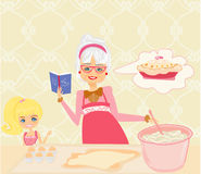 Grandma baking cookies with her granddaughter Royalty Free Stock Images