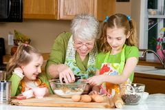 Grandma baking cookies in the kitchen. A gray haired Grandmother teaching kids how to bake cookies Stock Photos