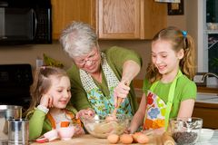 Grandma baking cookies in the kitchen. A friendly, gray haired Grandma baking cookies with two kids in the kitchen royalty free stock image