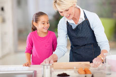 Grandma baking cookies. Loving grandma baking cookies for granddaughter at home Royalty Free Stock Photos