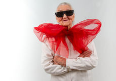 Grandma with a bizarre style. Very old lady with a  huge red bow and  eyeglasses Royalty Free Stock Image