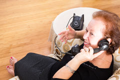Grandma chatting on an old rotary telephone. Grandma sitting in a comfortable armchair at home chatting on an old rotary telephone and smiling happily as she royalty free stock photography