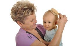 Grandma combing grandchild Stock Image
