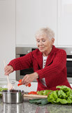 Grandma cooking. Happy active grandma is cooking lunch for family royalty free stock photo