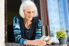 Grandma counting retirement money at home. On the window at home Royalty Free Stock Images