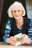 Grandma counting retirement money at home. On the window at home Stock Image