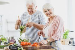 Grandma cuts pepper and grandpa mixes salad. Grandma cuts pepper and grandpa mixes vegetable salad during cooking together in white kitchen royalty free stock image