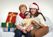 Grandma, daughter and granddaughter dressed in santa hat with gift boxes sit on sofa, white background. New year eve and christmas Royalty Free Stock Images