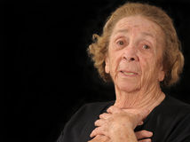 Grandma in dismay. An elderly woman clutching her chest in dismay stock photo