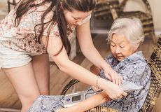 Grandma doing a check-up on the health at home. Grand daughter checking the blood pressure of her diabetic obaasan grandma. Japanese descendant Stock Photo