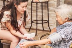 Grandma doing a check-up on the health at home. Grand daughter checking the blood pressure of her diabetic obaasan grandma. Japanese descendant Royalty Free Stock Photo
