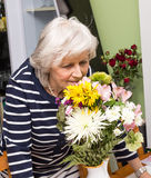 Grandma enjoys retirement and smelling flowers. Woman showing that she enjoys retirement by relaxing and smelling flowers stock images