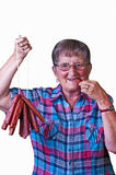 Grandma enjoys smoked sausage Royalty Free Stock Photography