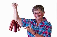 Grandma enjoys smoked sausage Stock Image
