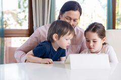 Grandma entertaining her little grandchildren with a tablet computer game. Young grandmother playing computer games on tablet with her little grandchildren royalty free stock image