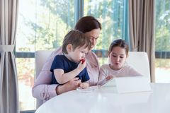 Grandma entertaining her little grandchildren with a tablet computer game. Young grandmother playing computer games on tablet with her little grandchildren royalty free stock images