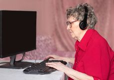 Grandmother in the modern world. Not a day without the Internet. Grandmother works for computer with interest learning a new computer program stock images
