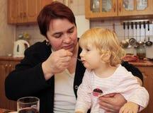 Grandma fed her granddaughter Stock Images