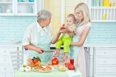 Grandma feeds the child vegetarian products. Royalty Free Stock Photos
