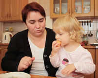 Grandma feeds granddaughter tangerine Royalty Free Stock Photography