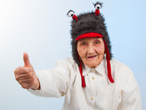 Grandma in funny hat shows thumbs up. Very old lady in funny fur hat with two tentacles showing thumbs up Royalty Free Stock Photo