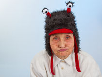 Grandma in funny hat with a sulky expression Stock Image