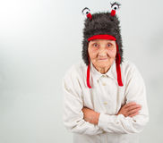 Grandma in funny hat. Very old lady in funny fur hat with two tentacles Royalty Free Stock Photo