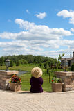 Grandma gardener taking a break to admire the view. Sitting with her back to the camera on the steps of her paved patio enjoying the scenic lush green royalty free stock images
